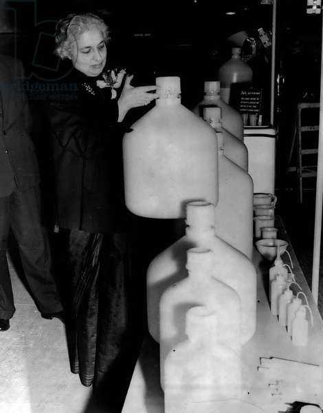 """Jan. 01, 1955 - Opening Of The Packaging Exhibition. Mrs. Pandit With Polythene Carboy: The new High Commissioner for India Mrs. Vijaya Lakshmi Pandit sister of the Indian Prime Minister- accompanied the Lord Privy Seal- Capt. RT. Hon.H. Crookshank M.P. when he opened the fourth National Packaging Exhibition which is being held at Olympia- this morning. Picture Shows: Mrs. ViJaya Lakshmi Pandit tries the weight of a"""" Skylon"""" Polythene Carboy- one f the new packaging items - at the Exhibition this morning"""