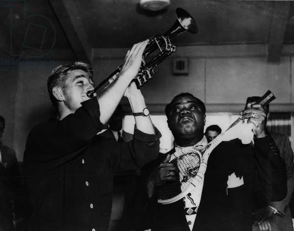 Nov. 11, 1954 - Lewis and Louis do a swap. Soon after Louis Armstrong arrived in Sydney recently - Australian tennis star Lewis Hoad Joined up with him for a jam session. The famous pair, seen at Mascot airport, Sydney, created quite a bit of fun with their good - matured clowning - when they exchanged trumpet and racket