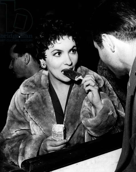"""Jan. 01, 1955 - She Loves A 'Lolly' - Does Lollo...!!! Italian Star Visits The Circus: Popular star of the Italian Screen Lovely Gina Lollobrigida was the guest of honor at the Circus Togni, nr. Rome recently - at a benefit performance for the poor of the Italian Capital. During the interval - Gina Petted a newly born lion club - ate a sweet 'Lolly' - and met Tiberio Mitri idol of the Italian boxing enthusiasts. Phoot Shows Gina Lollobrigida really enjoys a sweet"""" Lolly"""" during her visit to the Circus"""