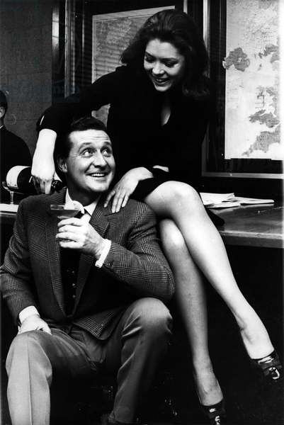 "Nov. 25, 1965 -"" the avengers"" Patrick Macnee and Diana Rigg celebrate the news, their television series has been sold to the United States with a drink of champagne"