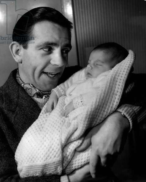 Jan. 01, 1955 - Norman Wisdom And Baby Jacqueline: Photo Shows Famous Comedian, Norman Wisdom, seen as he tenderly holds his baby daughter, Jacqueline - at his Barnet home