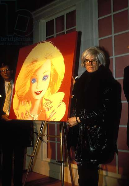 Portrait of American artist Andy Warhol posing near one of his works in February 1987 (photo)