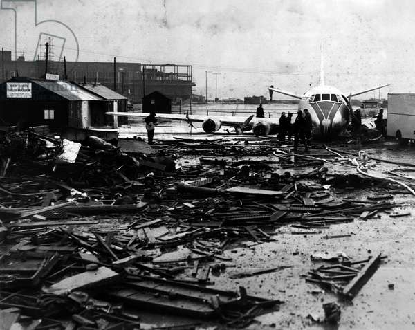 Jan. 01, 1955 - Two Injured As B.E.A. Viscount Airliner Crashes On Take-Off At London Airport. The pilot and one passenger were injured when a B.E.A. Viscount airliner crashed on the take-off at London Airport. The aircraft had taken a wrong turning on to a disused runway in mistake for the main take-off runway during the fog. It crashed into a barrier and ended up between a hangar and some builder's huts. One engine was thrown on to a stack of scrap metal. There were 25 passengers aboard the aircraft including two children. Keystone Photo Shows: - The scene at London Airport showing the damaged plane amid the wreckage of the huts